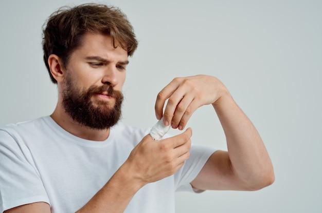 Homme malade bandé blessure à la main aux doigts fond clair