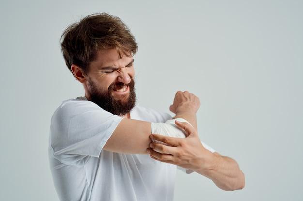 Homme malade bandé blessure à la main aux doigts hospitalisation fond clair