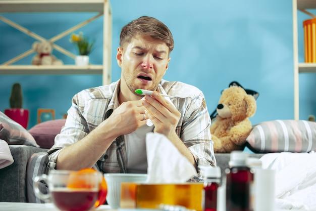 Homme malade barbu avec cheminée assis sur un canapé à la maison et mesurer la température corporelle. l'hiver, la maladie, la grippe, le concept de la douleur. détente à la maison