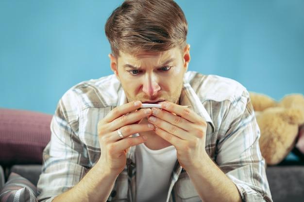 Homme malade barbu avec cheminée assis sur un canapé à la maison et mesurer la température corporelle.