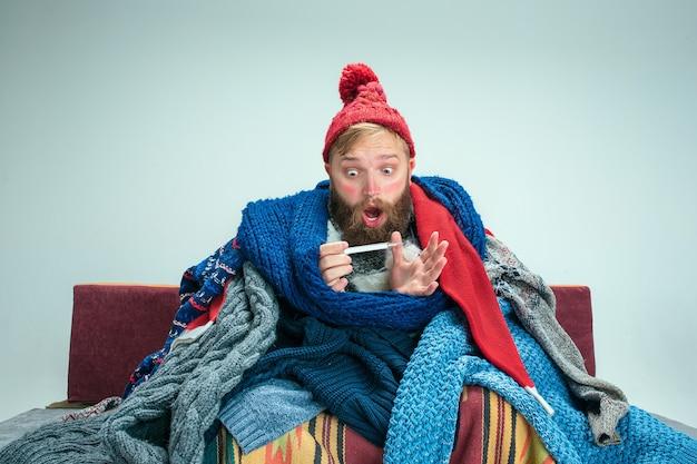 Homme malade barbu avec cheminée assis sur un canapé à la maison ou en studio avec thermomètre recouvert de vêtements chauds tricotés. maladie, concept de grippe. détente à la maison. concepts de santé.