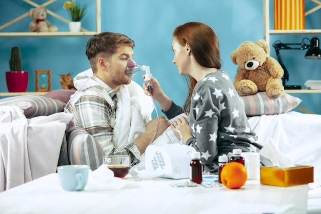 Homme malade barbu et sa femme assis sur un canapé à la maison recouvert d'une couverture chaude et utilisant un inhalateur pour tousser.