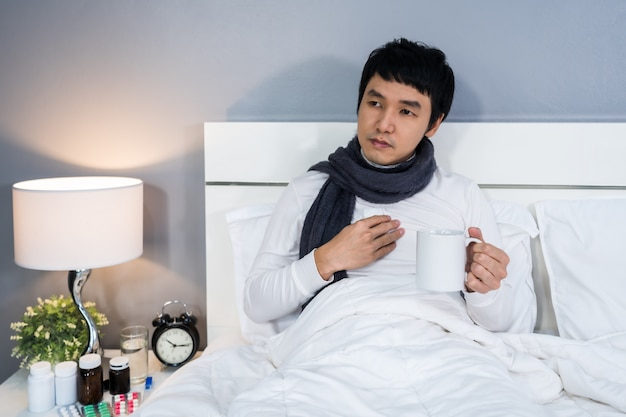 Homme malade, boire une tasse d'eau chaude sur le lit