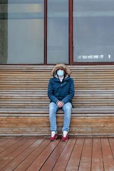 Homme malade avec une capuche assis seul sur un banc, portant un masque facial de protection. pandémie de coronavirus