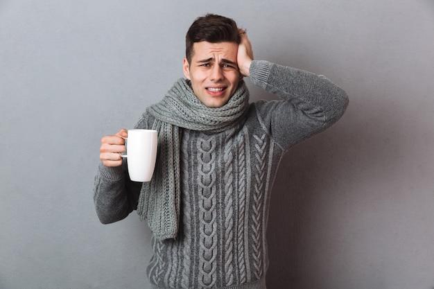 Homme malade confus en pull et écharpe ayant des maux de tête tout en tenant une tasse de thé et en regardant