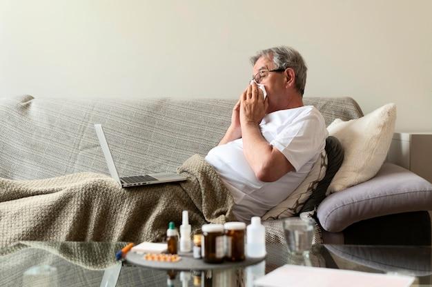 Homme malade de coup moyen sur un canapé avec un ordinateur portable