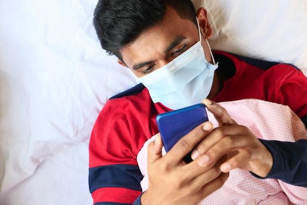 Homme malade dans un masque chirurgical à l'aide de la mise au point sélective de téléphone intelligent
