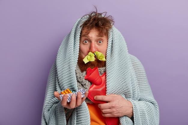 Homme malade dans des vêtements chauds avec des pilules et un sac d'eau