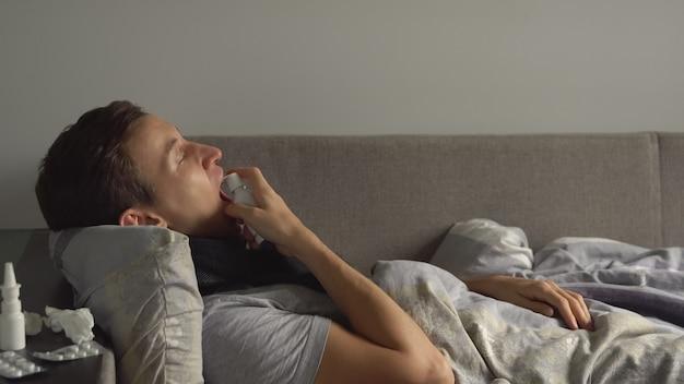 Un homme malade est allongé dans son lit à côté de ses médicaments dans sa maison et lui asperge un spray pour la gorge dans la gorge.