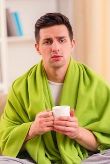 Un homme malade est assis à la maison et tient une tasse de café dans ses mains.