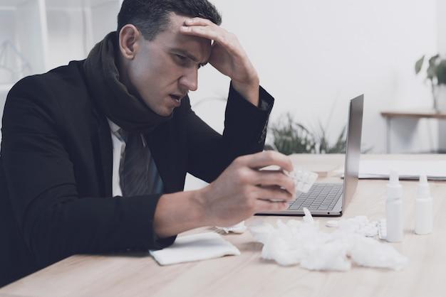 Un homme malade est assis sur son lieu de travail au bureau.