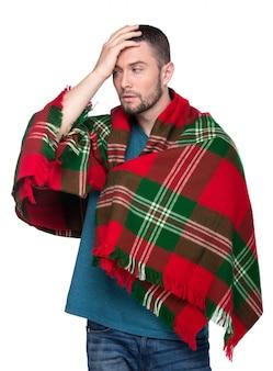 Un homme malade est couvert d'une couverture à carreaux