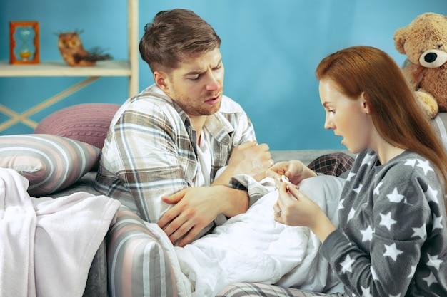 Homme malade avec fièvre couché dans son lit ayant de la température. sa femme s'occupe de lui. la maladie, la grippe, la douleur, le concept de famille. détente à la maison. concepts de santé.