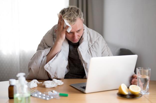 Homme malade avec fièvre restant à l'intérieur