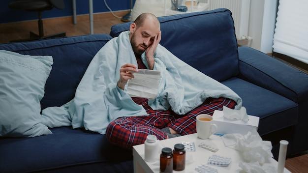 Homme malade lisant une notice d'information sur les médicaments