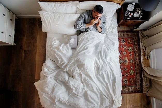 Homme malade sur le lit en train de se moucher