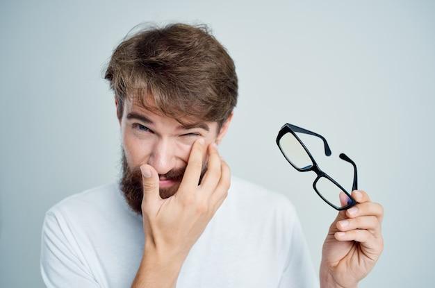Homme malade avec des lunettes à la main des problèmes de vision fond clair