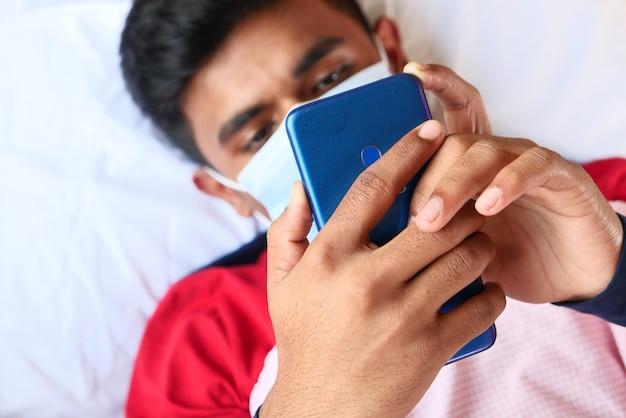 Homme malade en masque chirurgical à l'aide de téléphone intelligent, mise au point sélective,