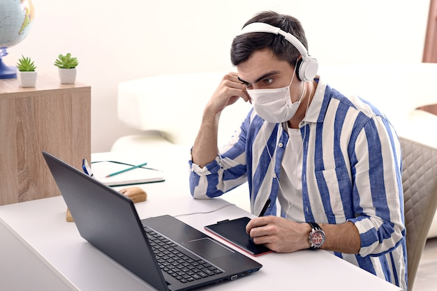 Homme malade en masque médical et casque travaillant sur ordinateur portable, travail à distance en quarantaine à la maison, concept de pigiste