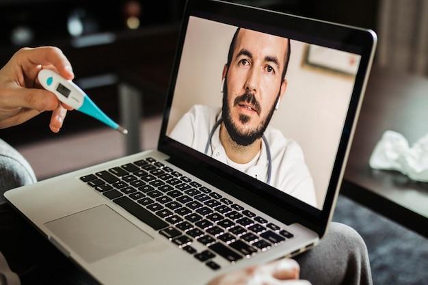 Homme malade parlant à son médecin par vidéoconférence tout en vérifiant la fièvre avec un thermomètre