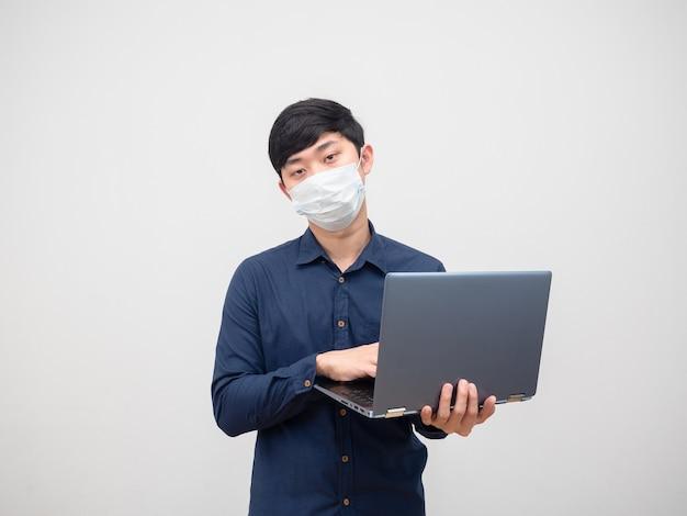 Homme malade portant un masque à l'aide d'un ordinateur portable dans sa main visage malheureux sur fond blanc
