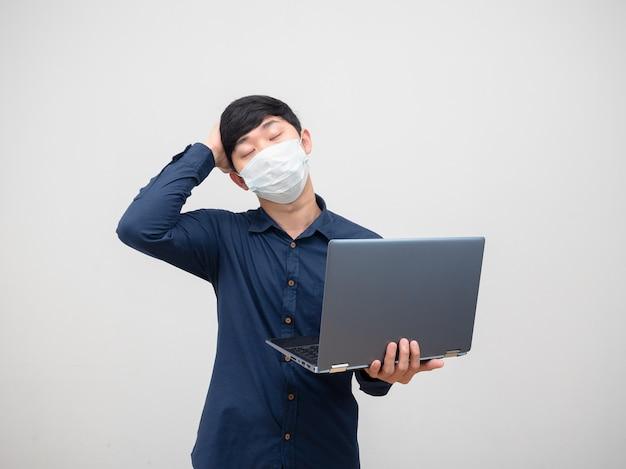 Homme malade portant un masque se sentant mal à la tête tenant un ordinateur portable à la main sur fond blanc