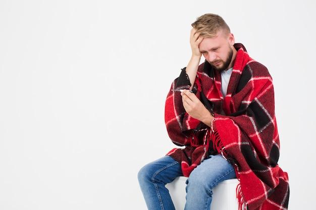 Homme malade en regardant un thermomètre