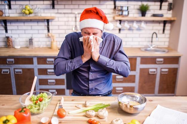 Un homme malade s'asseoir à table dans la cuisine.
