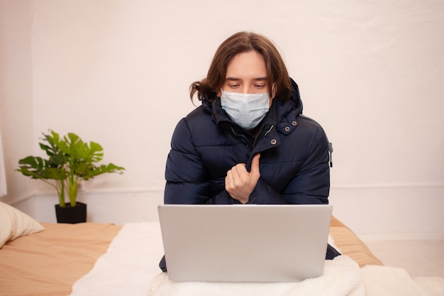 Un homme malade s'est figé chez lui. c'est très froid. un homme est assis dans des vêtements extérieurs derrière un ordinateur portable portant un masque. quarantaine à domicile en hiver. coronavirus, covid.