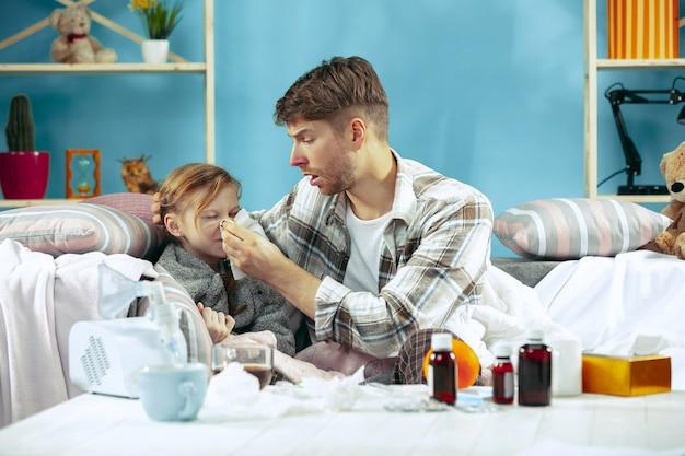 Homme malade avec sa fille à la maison. traitement à domicile. se battre avec une maladie. santé médicale. la vie de la famille. l'hiver, la grippe, la santé, la douleur, la parentalité, le concept de relation. détente à la maison