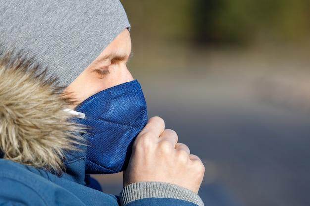 Homme malade en veste bleue avec un capuchon ayant un rhume, la toux et portant un masque médical