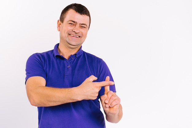 Un homme malentendant sourit et montre des signes de communication non verbale sur fond blanc. signe
