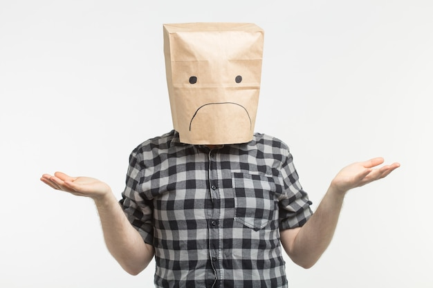 Homme malheureux avec une émoticône triste devant un sac en papier sur la tête sur fond blanc.