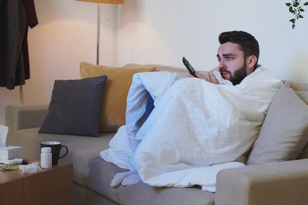 Homme malheureux et malade enveloppé dans une couverture assis sur un canapé devant la télévision et regarder un film tout en restant à la maison pour s'isoler