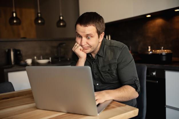 Un homme malheureux travaille à domicile. travailler sur un ordinateur portable à l'intérieur. travailleur en ligne, pigiste dans la cuisine