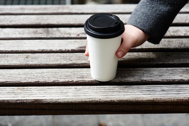 Homme avec une manche grise prend une tasse de café en papier
