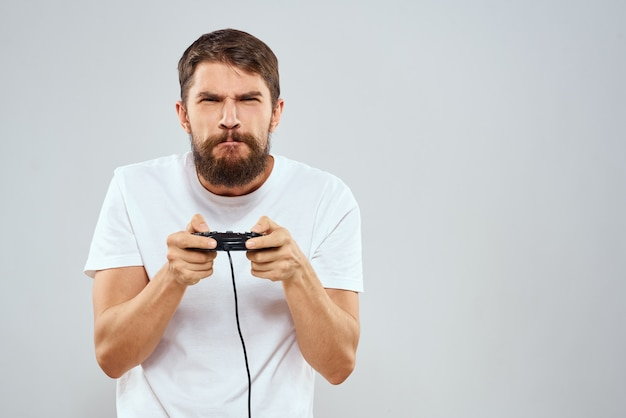 Un homme avec une manette de jeu dans ses mains en jouant à des jeux de loisirs mode de vie technologie t-shirt blanc fond clair.