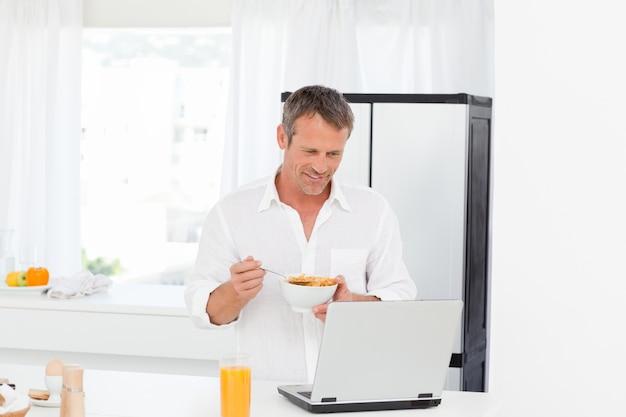 Homme mange des céréales pendant qu'il travaille sur son ordinateur portable