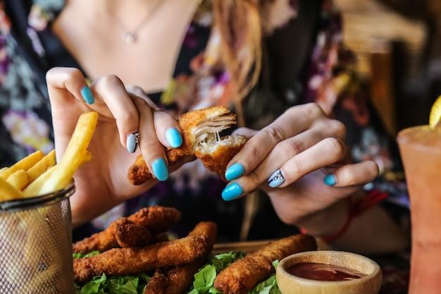 L'homme mange des doigts de poulet avec des frites vue de côté de ketchup