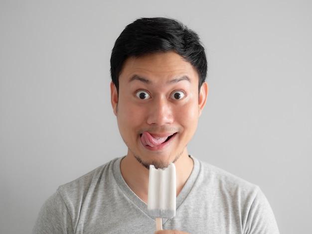 L'homme mange de la glace pop avec une drôle de tête.