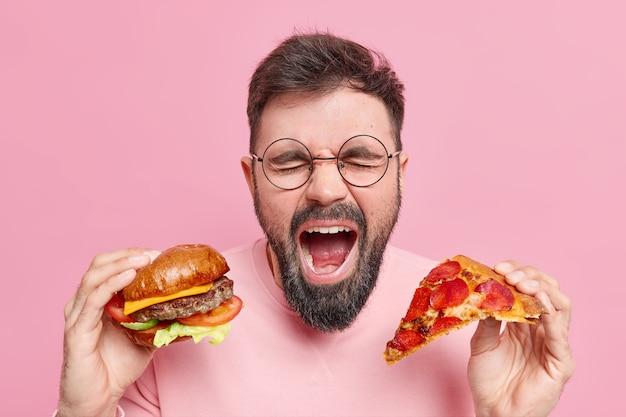 L'homme mange de la malbouffe crie fort garde la bouche largement ouverte tient un hamburger et une tranche de pizza exprime des émotions négatives porte des lunettes rondes pull décontracté. concept de frénésie alimentaire