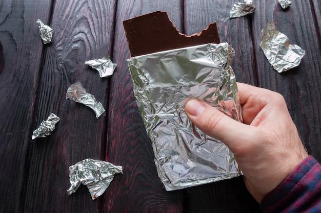 Homme mangeant une barre de chocolat noir