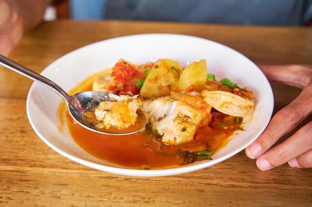 Homme mangeant avec une cuillère d'une casserole avec de la morue et des crevettes avec des pommes de terre et de l'aïoli au poivre de palme dans une table en bois