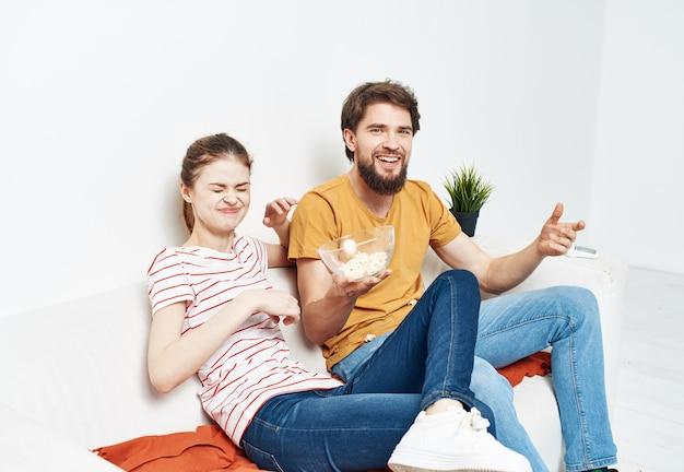 Homme mangeant du pop-corn et jolie femme dans une salle lumineuse communication entre amis de la famille