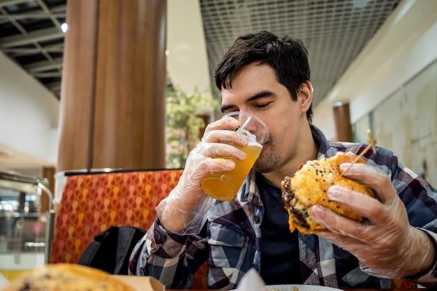 Homme mangeant un hamburger de restauration rapide et buvant de la bière seul dans l'espace ouvert d'un restaurant dans un centre commercial.