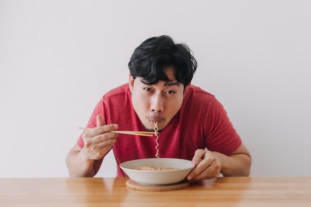 Homme mangeant des nouilles instantanées très délicieusement