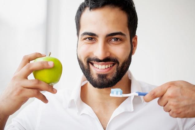 Homme mangeant des pommes. belle fille avec des dents blanches mordantes pomme.