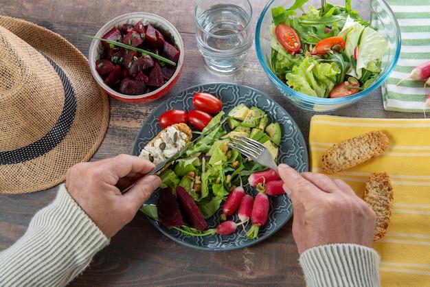 Homme mangeant une salade végétalienne. divers légumes avocat, radis sur fond en bois