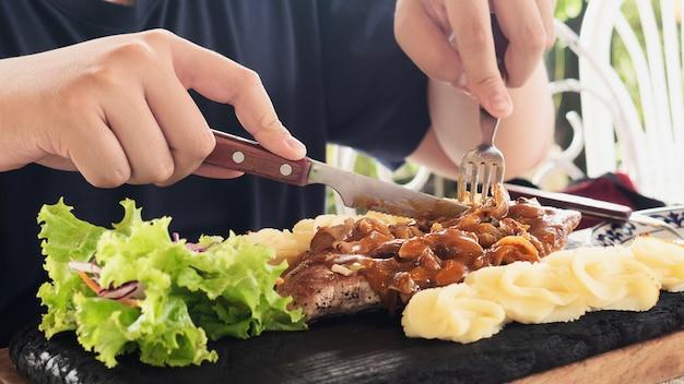 Homme mangeant un steak de porc