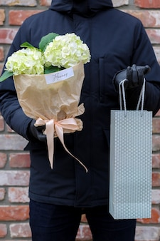 Homme en manteau noir tenant des fleurs et un sac
